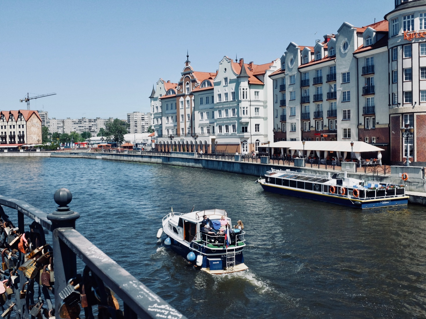 The Pregolya River in Kaliningrad, Russia, that connects to the Baltic Sea, with boat and neoclassical facades.