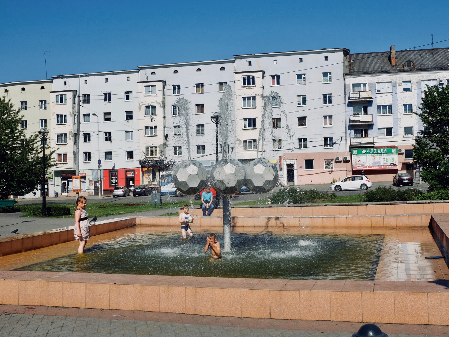 Fountain in Kaliningrad, Russia, where children play on a summer day.