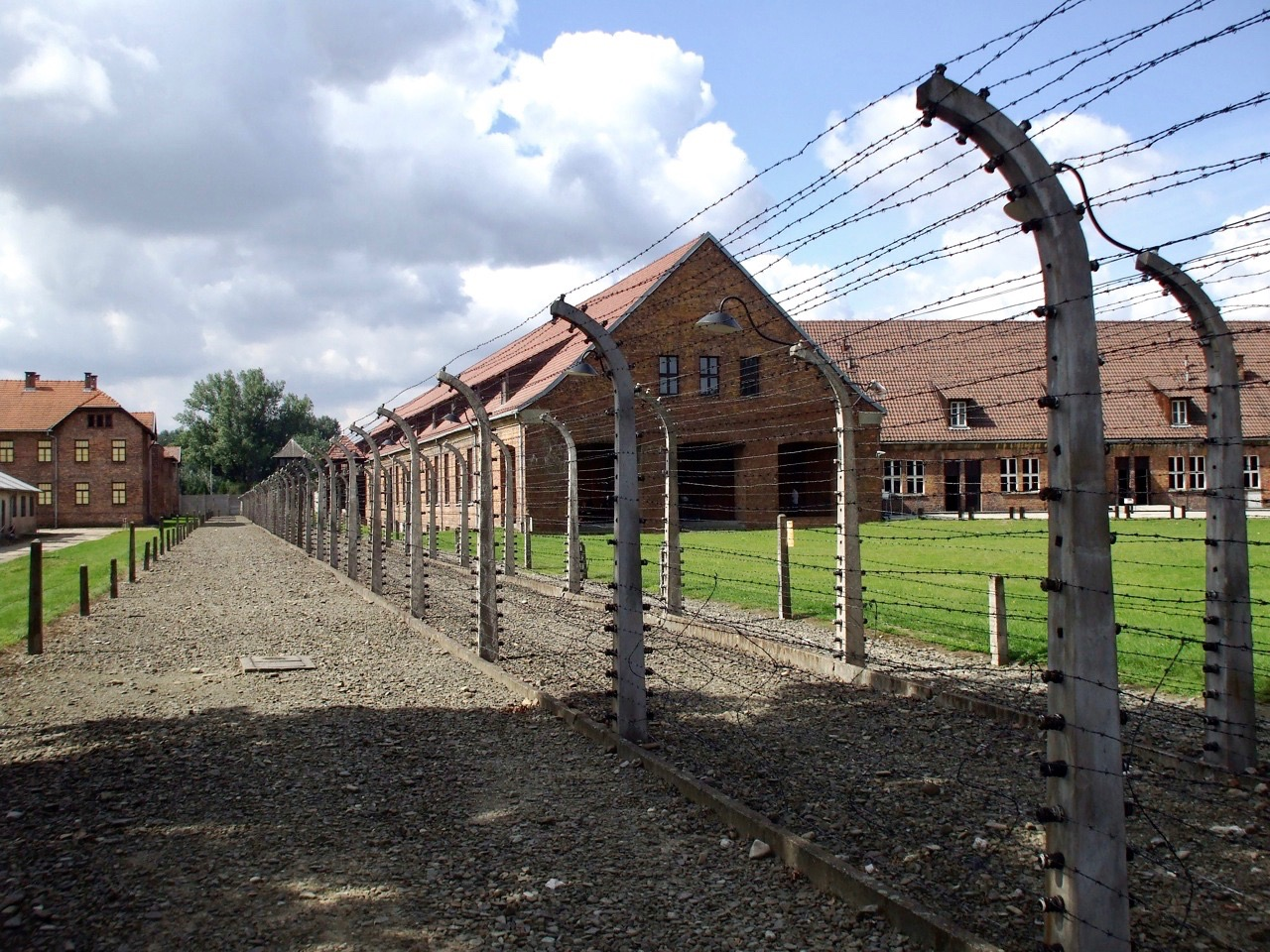 A view of brick buildings and green fields along a barbed wire fence at the former German Nazi Concentration and Extermination Camp at Auschwitz-Birkenau, in Oświęcim, Poland.