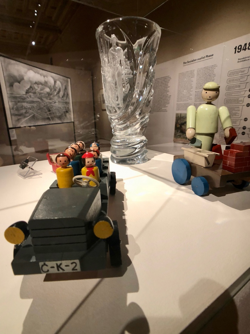 Socialist-Realism imagery was typically used in everyday objects, like toys and glassware. Images of workers are etched into this glass vase on display.