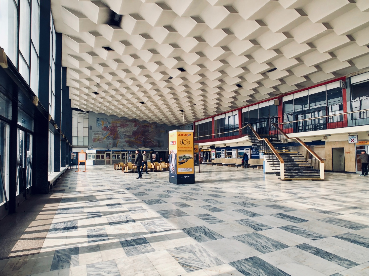 The main lobby at the train station as it appears today, with geometric patterns on the ceiling and floor, in the Czech-Silesian mining city of Havířov, Czech Republic.