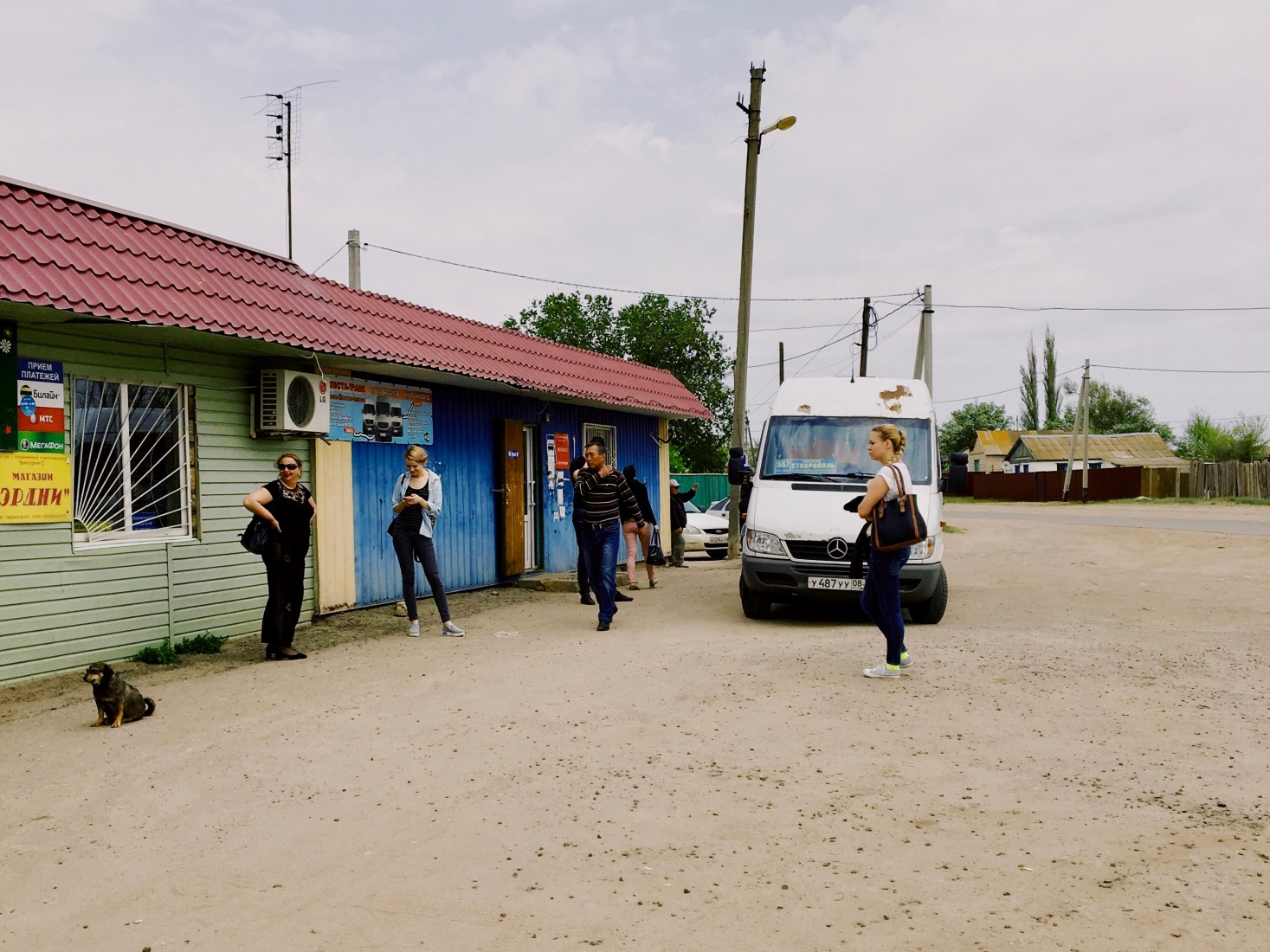 Minibus passengers walk around an empty dirt parking lot on a break during the five-hour drive through the steppe from Volgograd to Elista, Russia, in Kalmyk territory.