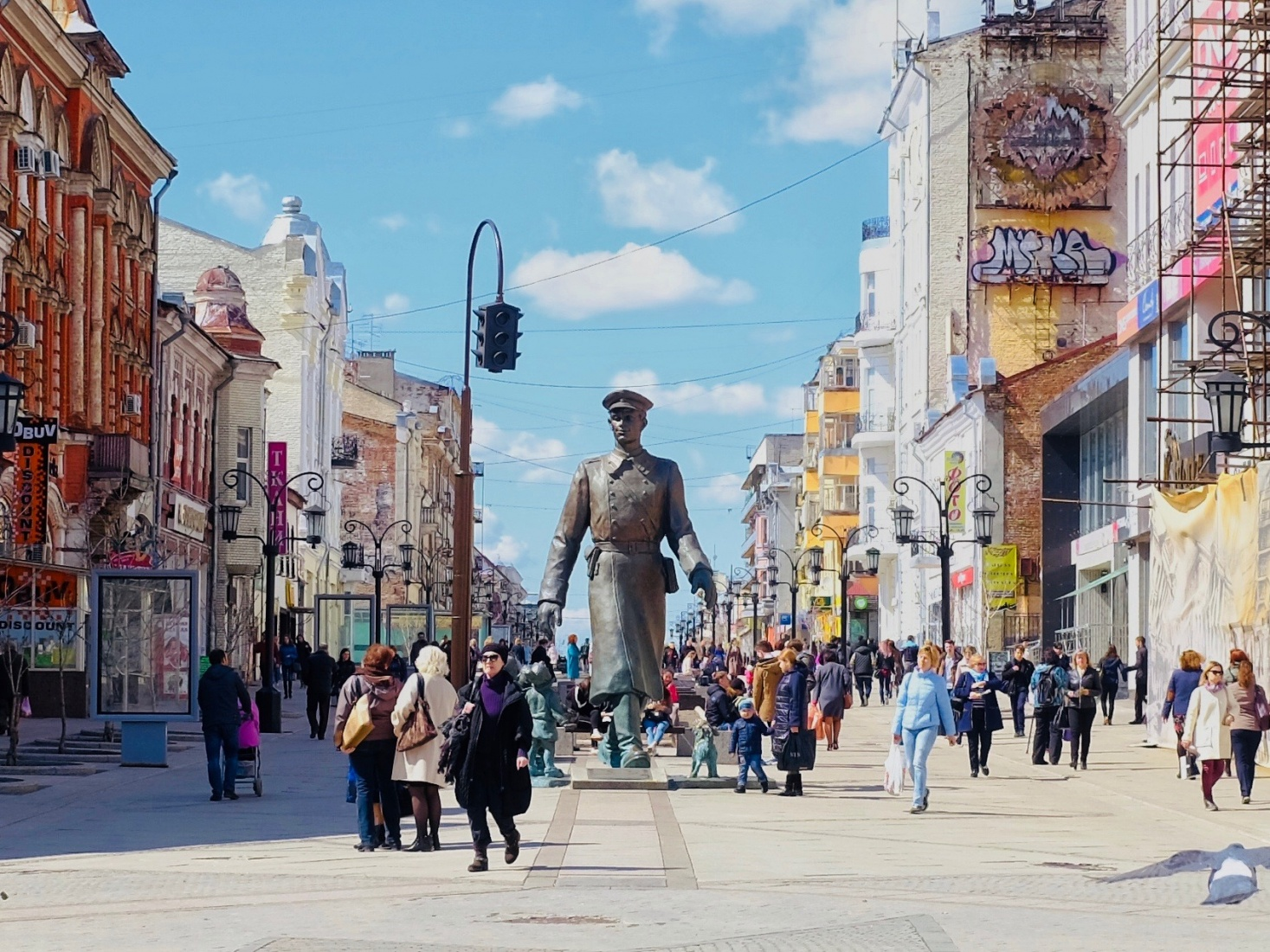 Larger than life statue of a man in Soviet-era uniform on busy street in downtown Samara, Russia.