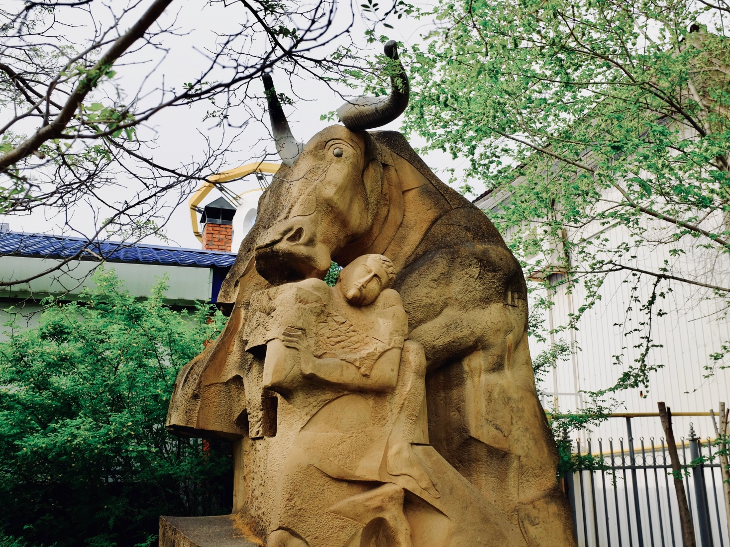 Sculpture on the sidewalk of Elista, Russia, depicting a man and a large horned mammal, possibly a Kalmyk cattle.