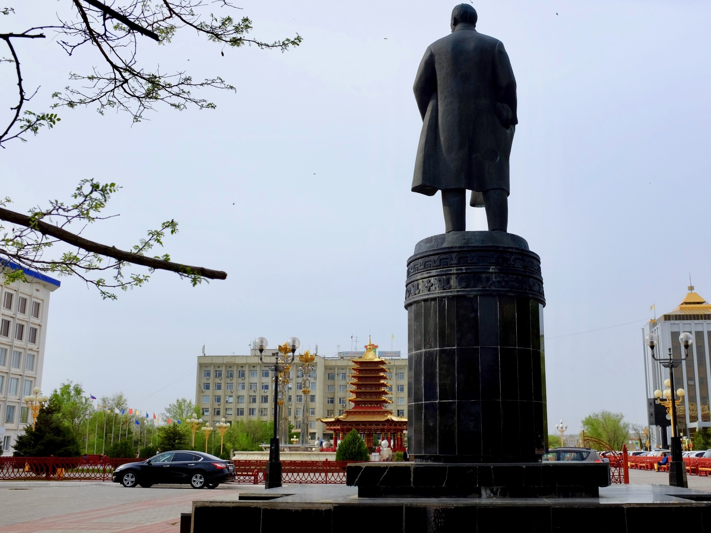 A statue of Lenin on Elista, Russia's central square, the bright Pagoda of the Seven Days in the background.