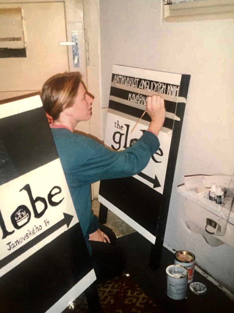 Markéta Rogers painting the sign that would stand outside The Globe Bookstore and Coffeehouse in Holešovice, Prague. Photo courtesy of Scott and Markéta Rogers.