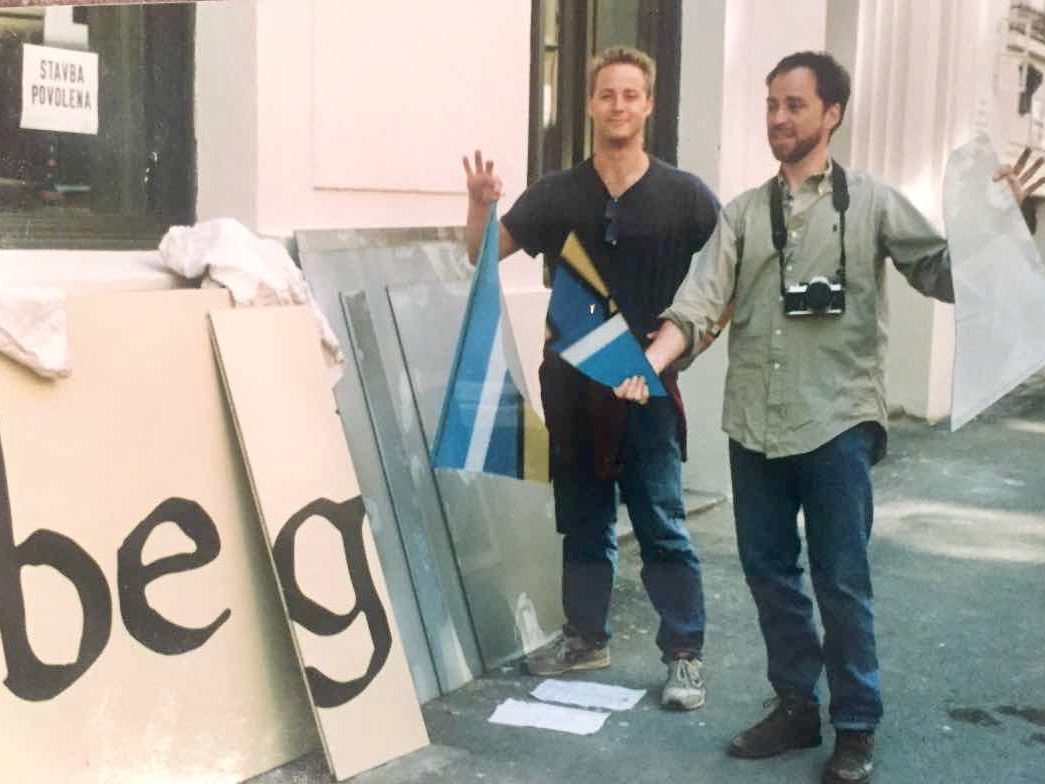 Jasper Bear and Mark Baker standing outside The Globe Bookstore and Coffeehouse while hanging signs and doing further renovations. Holešovice, Prague, May/June 1993. Photo courtesy of Scott and Markéta Rogers.