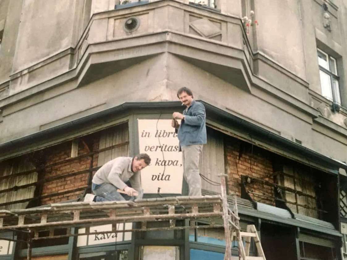 Putting up a large sign with The Globe Bookstore and Coffeehouse motto, 'In libris, veritas; in kava, vita', in Holešovice, Prague, 1993. Photo courtesy of Scott and Markéta Rogers.