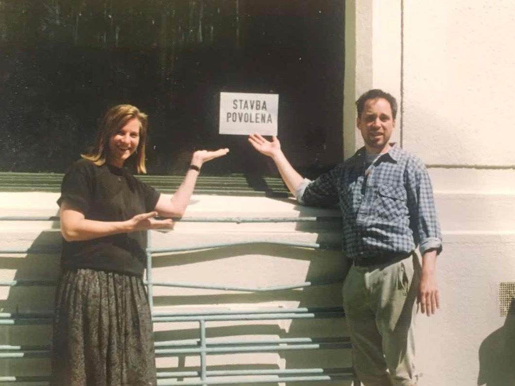 Markéta Rogers and Mark Baker in front of the store front of The Globe Bookstore and Coffeehouse in Holešovice, Prague, sign proving city approval. 1993. Photo courtesy of Scott and Markéta Rogers.