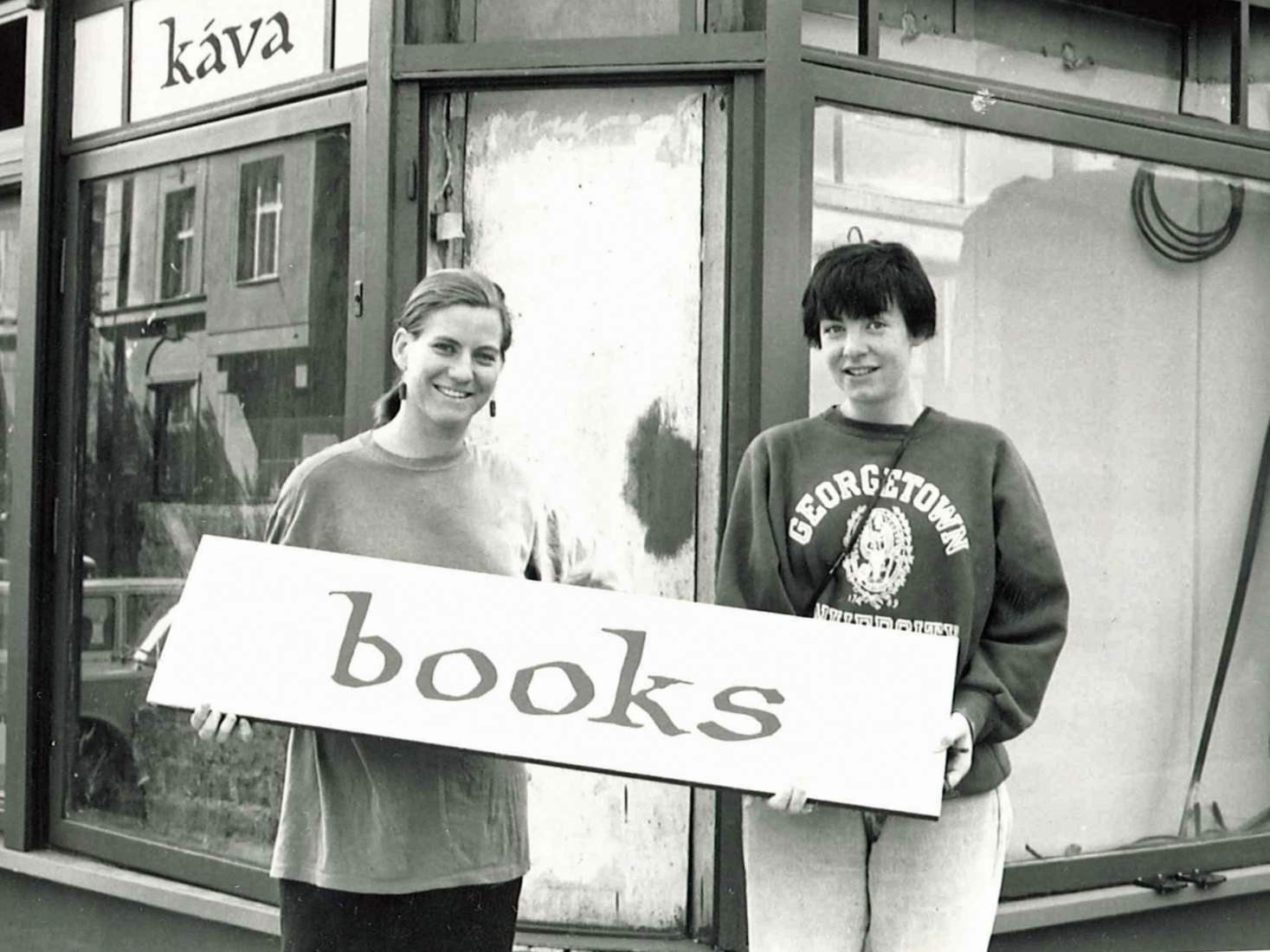 Market Rogers and Maura Griffin holding a sign from The Globe Bookstore and Coffeehouse facade, late spring 1993, Holešovice, Prague.