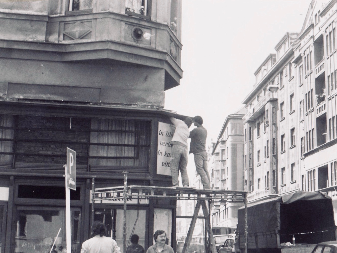 Renovating the outside of The Globe bookstore and cafe in 1993, putting up sign with store motto