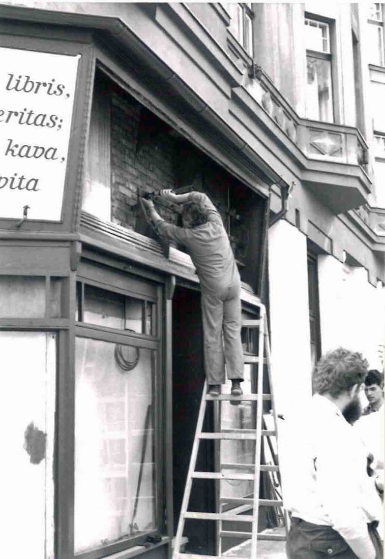 Worker Milan stripping old paint on the facade of The Globe Bookstore and Coffeehouse in Holešovice, Prague, 1993.