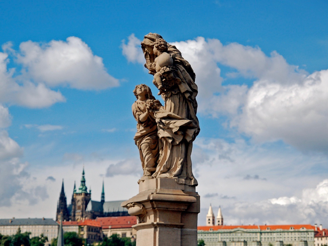 Baroque statues on the Gothic Charles Bridge, with Gothic towers of St. Vitus Cathedral and elements of Prague Castle in the background.