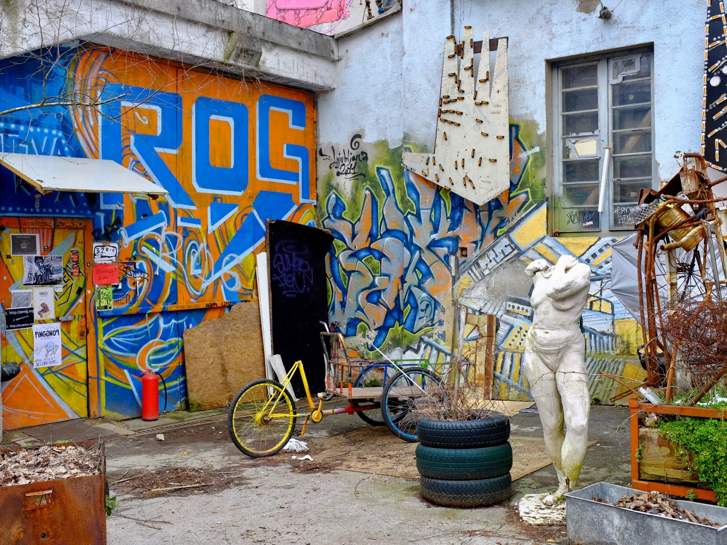 Graffiti covered walls, statue, and other street art at the Rog squat, former bicycle factory, near the Triple Bridge in Ljubljana, Slovenia.
