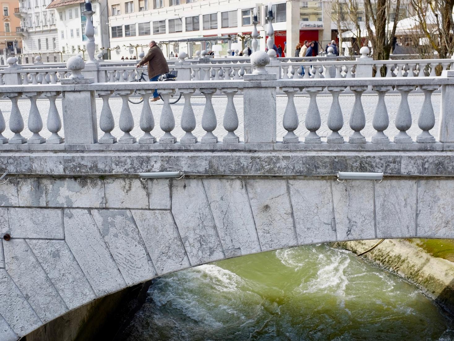 Decorative bridge designed by Jože Plečnik in Ljubljana, Slovenia, wtih pedestrian and classical seeming architecture over the green Ljubljanica River.