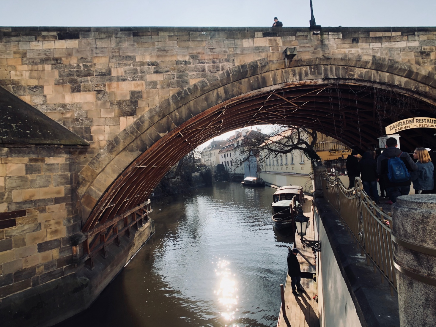 Underneath an arch of the Gothic Charles Bridge on the Certovka canal by Kampa Island, wooden reinforcements protecting boats.