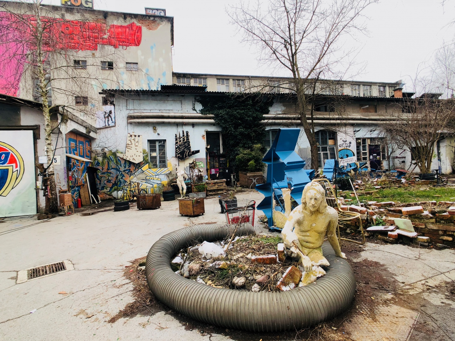 Street-art statue made of found materials and trash at Rog squat in Ljubljana, Slovenia, with graffiti and abandoned bicycle factory in the background.
