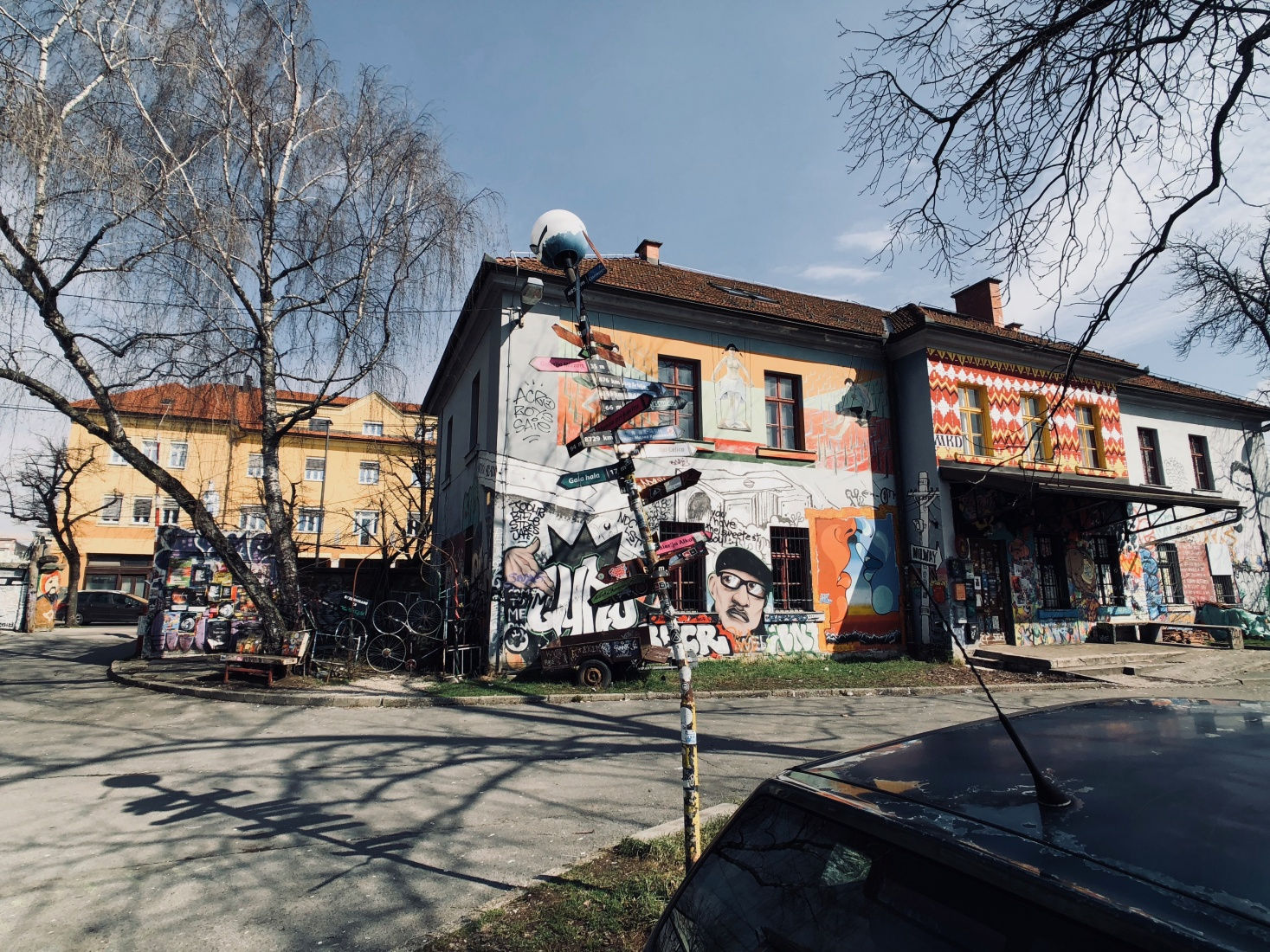 Street-art sign pointing students and visitors toward different clubs around Metelkova Mesto, a graffiti-covered squat in an abandoned military barracks in Ljubljana, Slovenia.