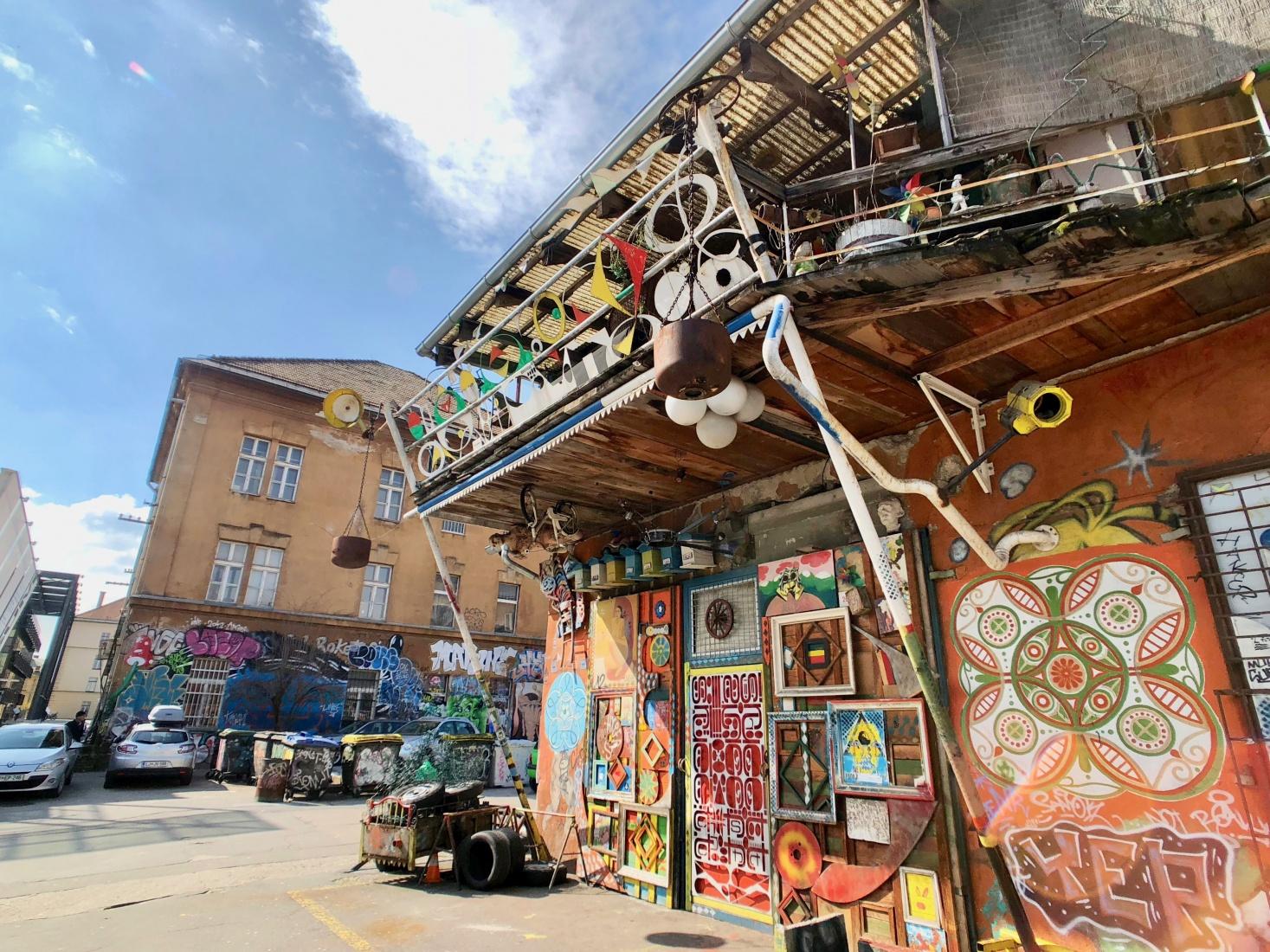 Graffiti-covered corner building at the Metelkova Mesto squat in Ljubljana, Slovenia, with street art in a residential area.