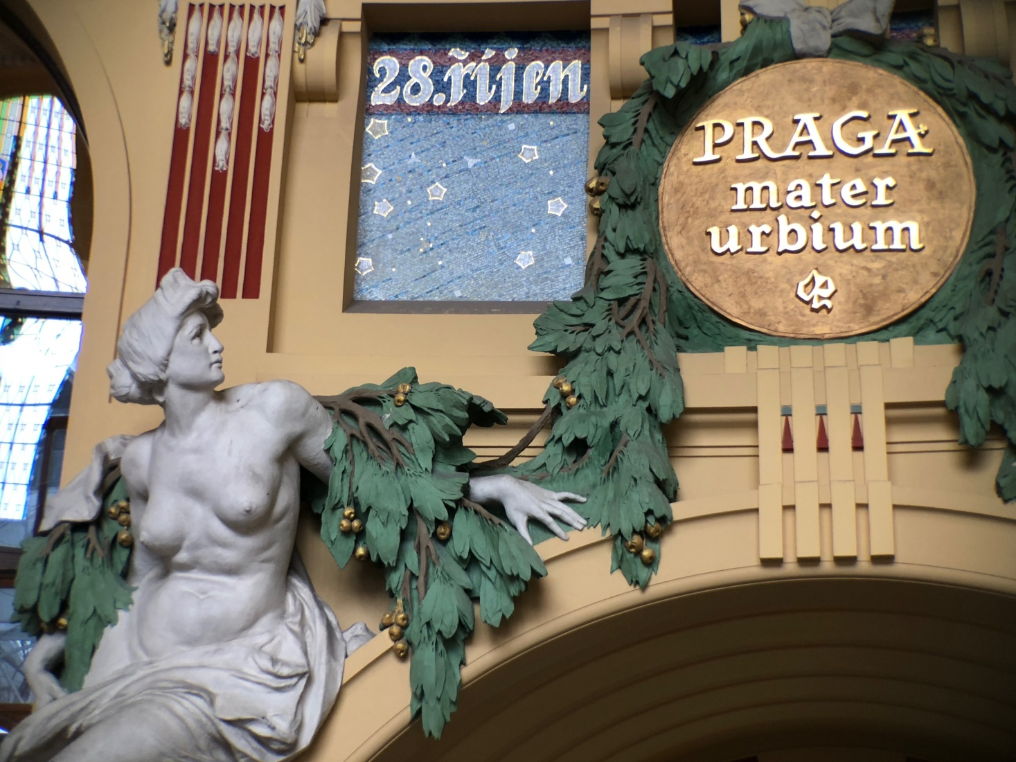 Detailed statue and emblem in the historic core of Prague main train station display influence of Parisian-style Art Nouveau.