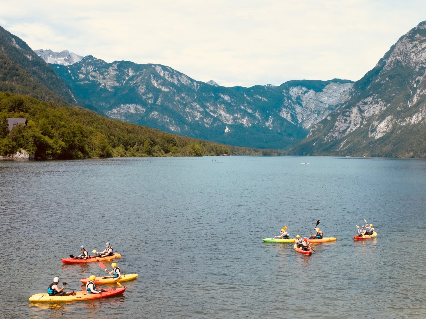 People kayaking on Lake Bohinj in Slovenia in June 2018, looking west from the lake's eastern shore.