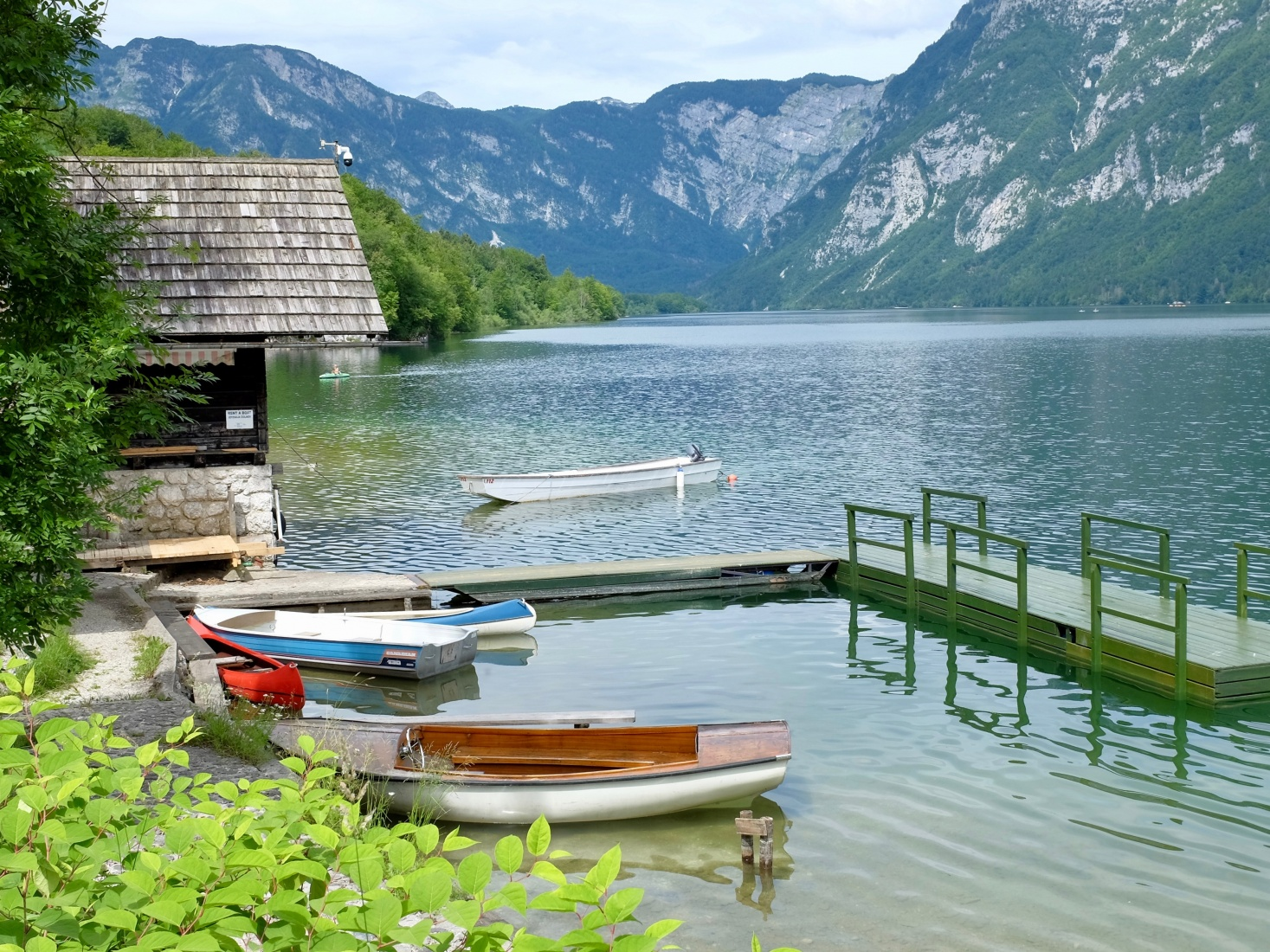 Boats, a dock, and a boathouse on Slovenia's Lake Bohinj, with clear water and beautiful distant mountains.