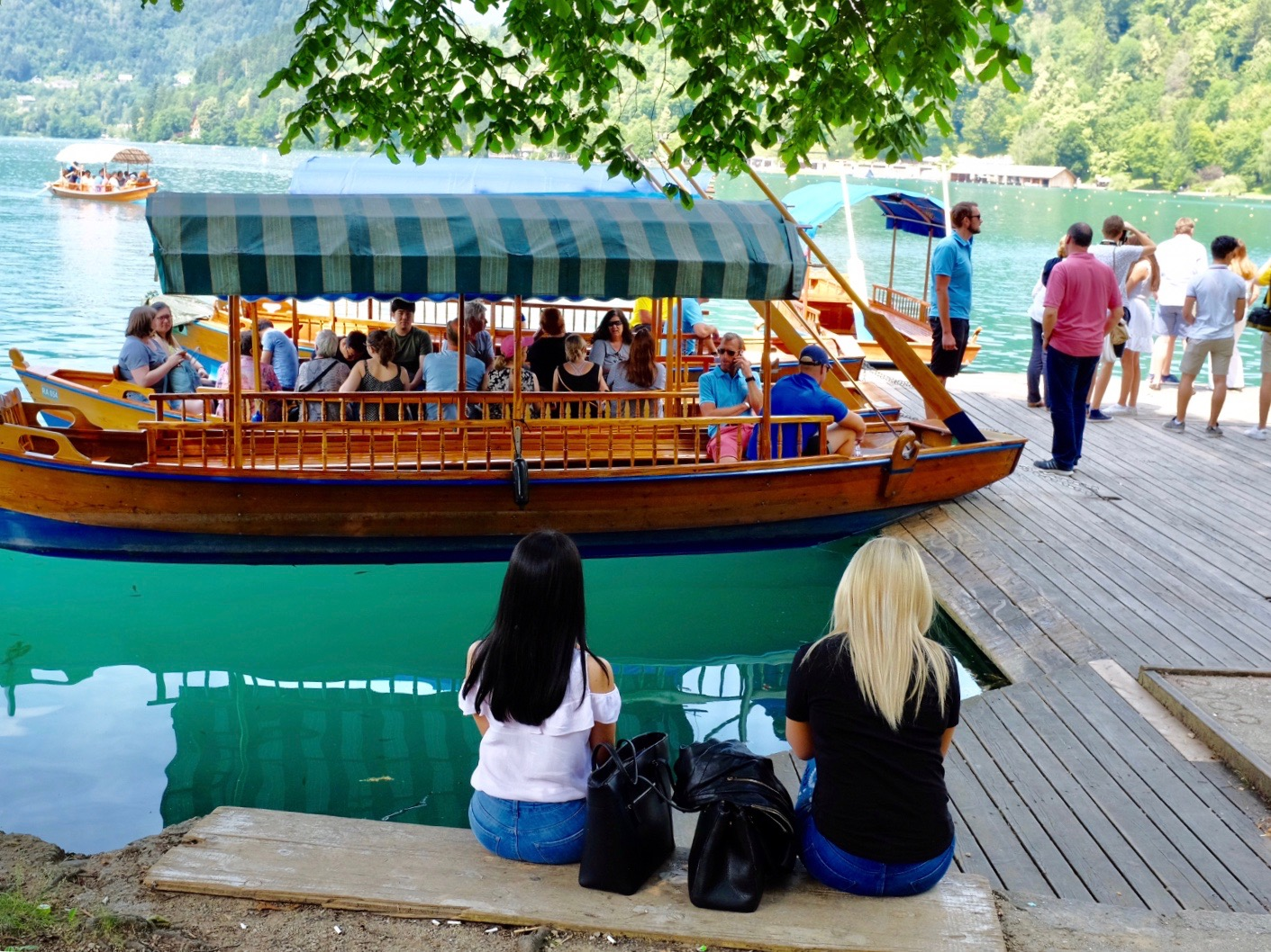 People watch a gondola boat of people launch at Lake Bled, Slovenia.