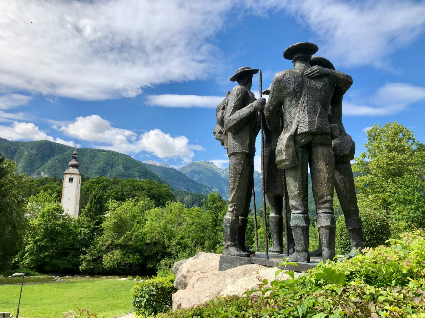 A statue of the original climbers of Mt. Triglav, who set out from Bohinj in 1778, with Triglav, Slovenia, in the background.