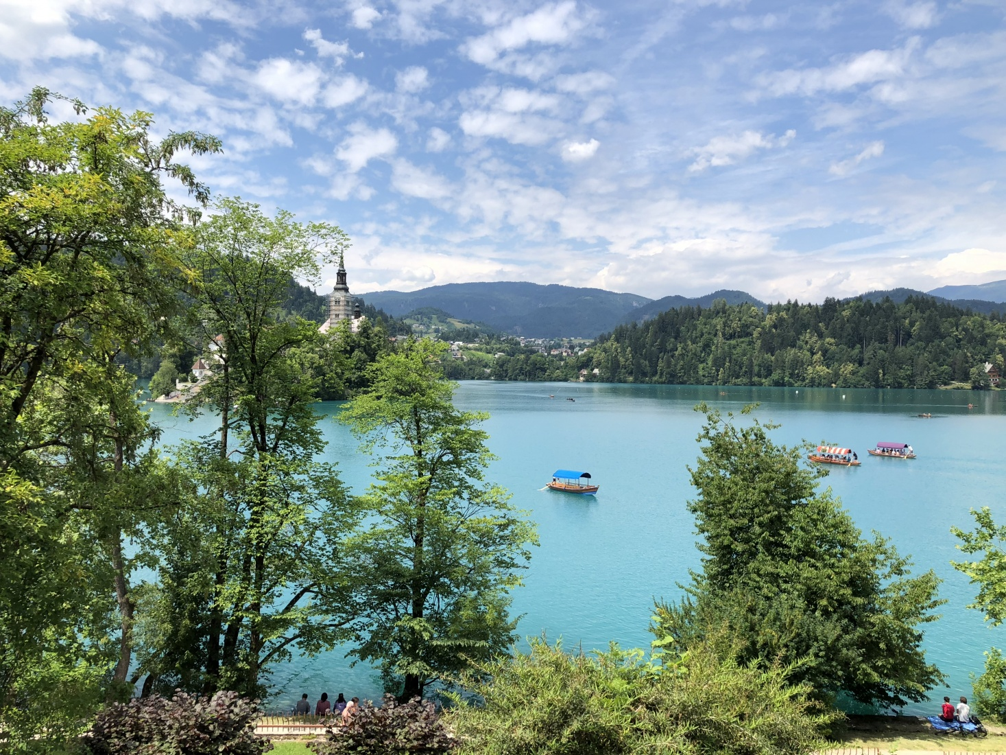 Lake Bled, Slovenia, boats on the lake and idyllic villages in the mountains.
