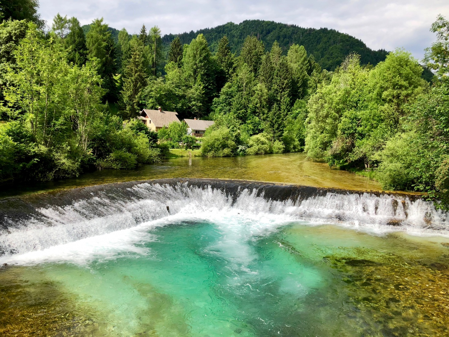 A stunning green-blue waterfall and waterway on the way out of Lake Bled, Slovenia, toward the Radovna Valley, near Krnica.