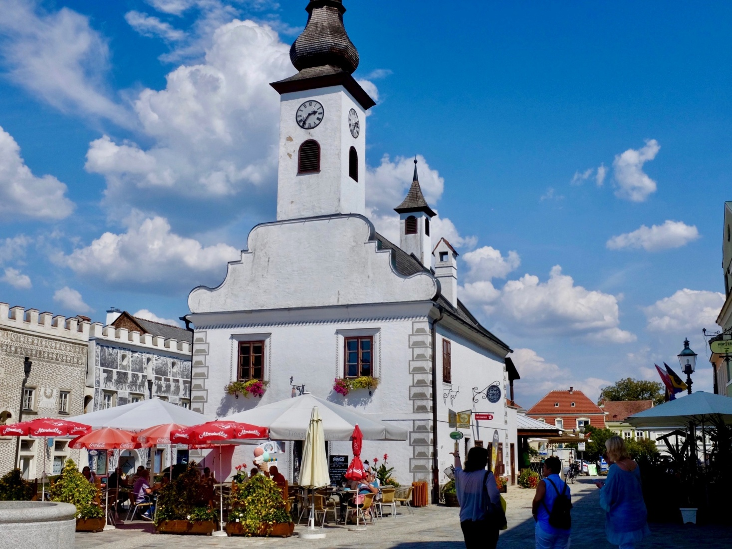 An old church and locals eating ice cream in the summer heat of Gmünd, Austria.