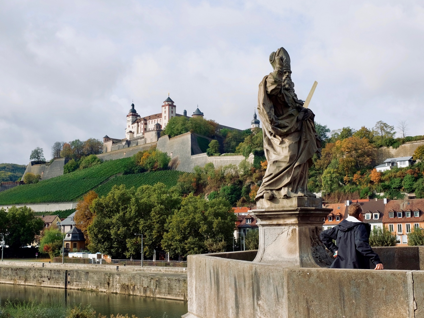 A statue on the bridge in Würzburg crossing the Main, with the ancient Marienberg fortress in the background.