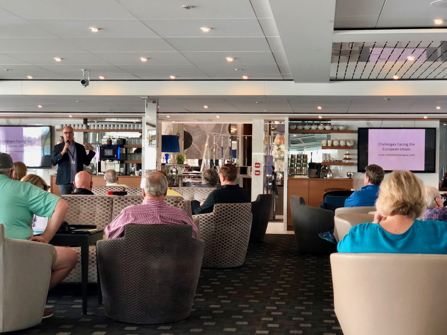 An audience of cruise passengers on the National Geographic ship listening to a lecture about the challenges facing the european union.